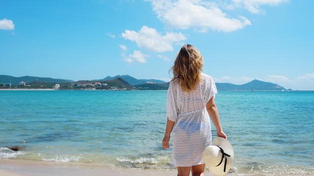 Mulher jovem com roupas brancas refrescantes na praia do oceano, china
