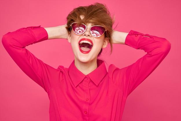 Mulher jovem com roupas brilhantes em um fundo rosa