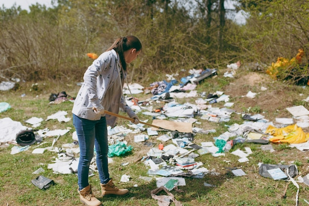 Mulher jovem com roupas casuais e luvas de látex para limpeza usando um ancinho para a coleta de lixo em um parque cheio de lixo