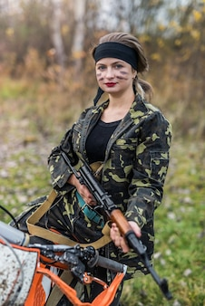 Mulher jovem com roupas de camuflagem e arma Foto Premium