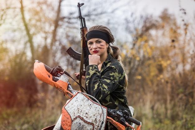 Mulher jovem com roupas de camuflagem e arma