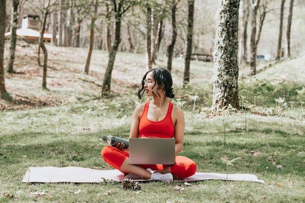 Mulher jovem com roupas de ginástica relaxando no laptop pegando uma garrafa de água no parque, sobre um tapete de ioga