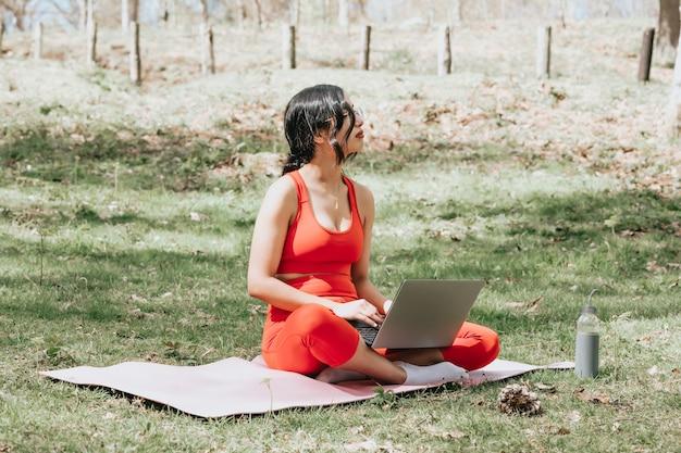 Mulher jovem com roupas de ginástica relaxando no laptop sorrindo para o parque, sobre um tapete de ioga