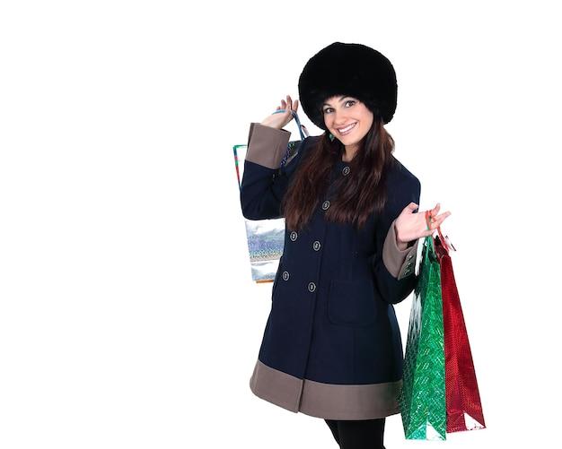 Mulher jovem com roupas de inverno com sacolas de compras isolada no fundo branco
