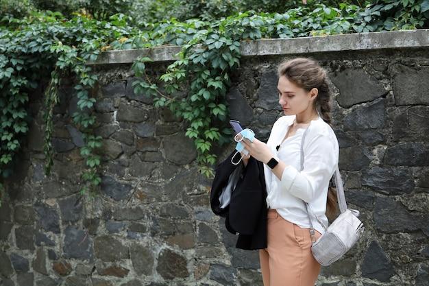Mulher jovem com roupas de negócios fica ao ar livre perto do muro de contenção e olha para o smartphone