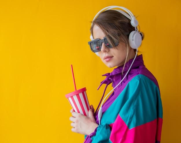 Mulher jovem com roupas estilo anos 90 com copo e fones de ouvido amarelo