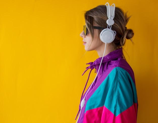 Mulher jovem com roupas estilo anos 90 com fones de ouvido amarelo
