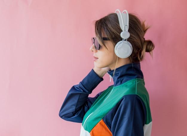 Mulher jovem com roupas estilo anos 90 com fones de ouvido rosa