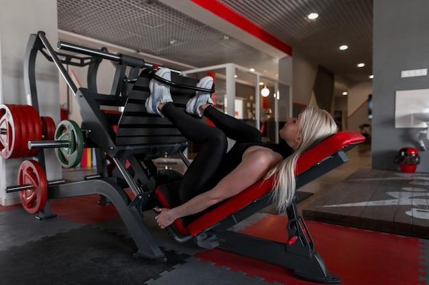 Mulher jovem com roupas pretas e tênis fazendo exercícios para as pernas deitada em um simulador moderno na academia