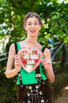Mulher jovem com roupas tradicionais da baviera ou calça comprida com um coração de lembrança de pão de gengibre no jardim de cerveja na oktoberfest