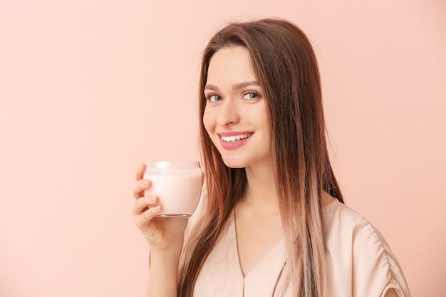 Mulher jovem com saboroso iogurte na superfície colorida