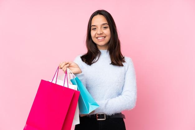 Mulher jovem com sacola de compras sobre fundo rosa isolado, mantendo os braços cruzados na posição frontal