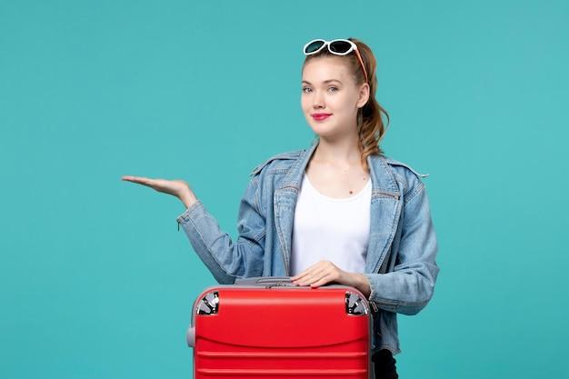 Mulher jovem com sacola se preparando para as férias no espaço azul claro