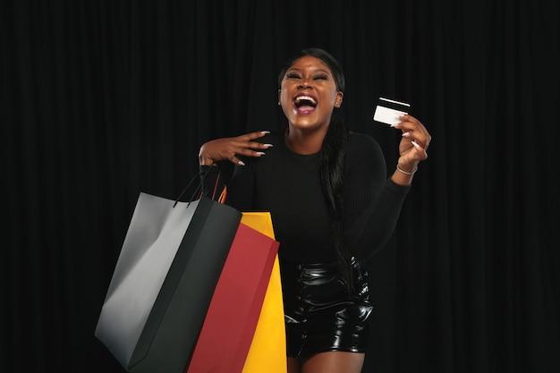 Mulher jovem com sacolas de compras e cartão de crédito