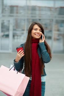 Mulher jovem com sacolas de compras saindo da loja e falando ao telefone