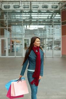 Mulher jovem com sacolas de compras saindo da loja