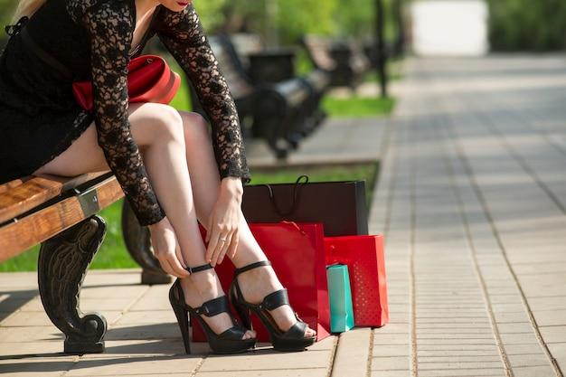 Mulher jovem com sacolas de compras, sentada em um banco do parque, show de férias