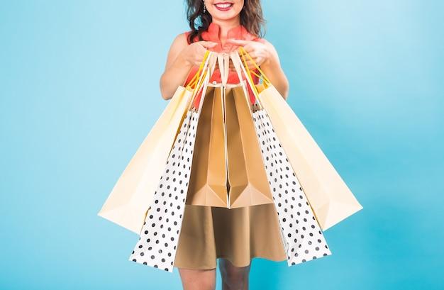 Mulher jovem com sacolas de compras sobre o azul