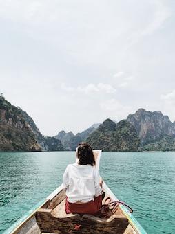 Mulher jovem com saia vermelha e blusa branca sentada em um barco de madeira, observando ilhas tropicais com pedras
