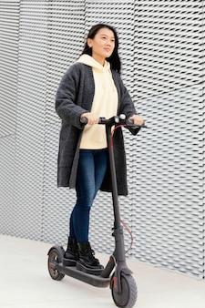 Mulher jovem com scooter elétrica