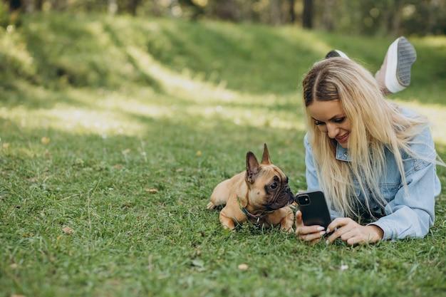 Mulher jovem com seu buldogue francês de estimação no parque