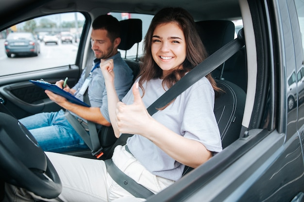 Mulher jovem com seu instrutor de automóvel em um carro