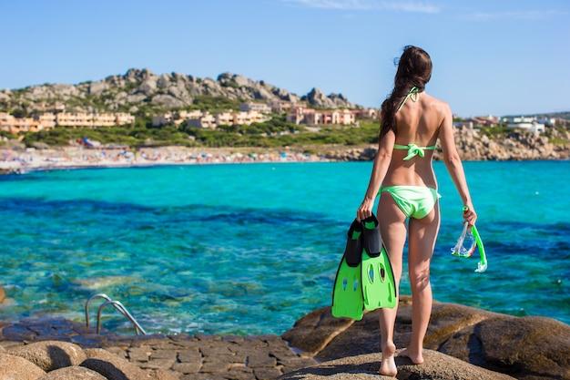 Mulher jovem, com, snorkeling, equipamento, ligado, pedras grandes, pronto, para, natação