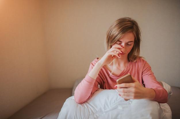 Mulher jovem com sono acordando com alarme. ela dormiu demais para trabalhar