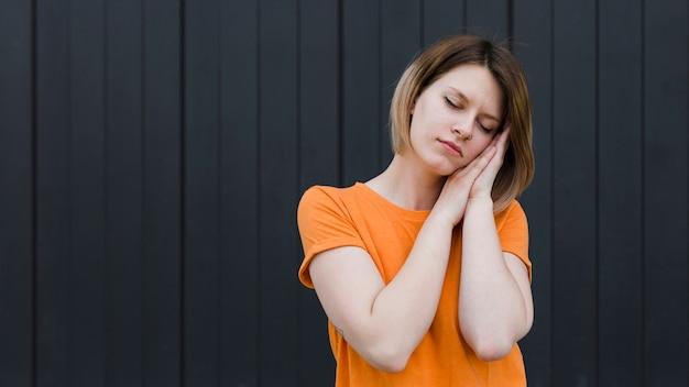 Mulher jovem com sono permanente contra o pano de fundo preto