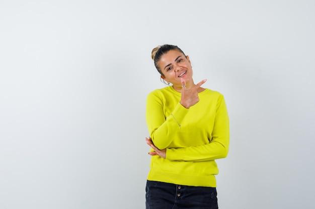 Mulher jovem com suéter amarelo e calça preta apontando para a direita com o dedo indicador e parecendo feliz