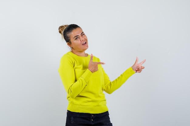 Mulher jovem com suéter amarelo e calça preta apontando para a direita com o dedo indicador, piscando e parecendo feliz