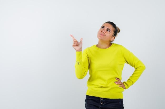 Mulher jovem com suéter amarelo e calça preta apontando para a esquerda, segurando a mão na cintura e parecendo pensativa