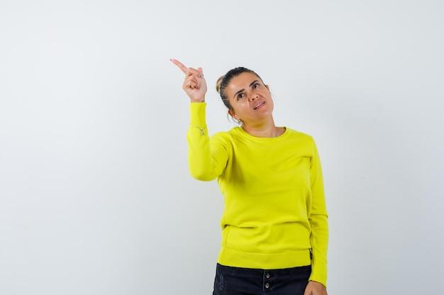Mulher jovem com suéter amarelo e calça preta apontando para cima e parecendo feliz