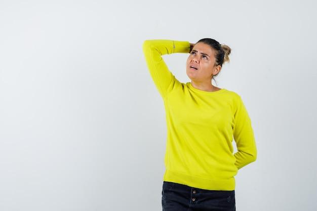 Mulher jovem com suéter amarelo e calça preta, colocando a mão na cabeça, enquanto mantém a mão atrás da cintura e parecendo pensativa