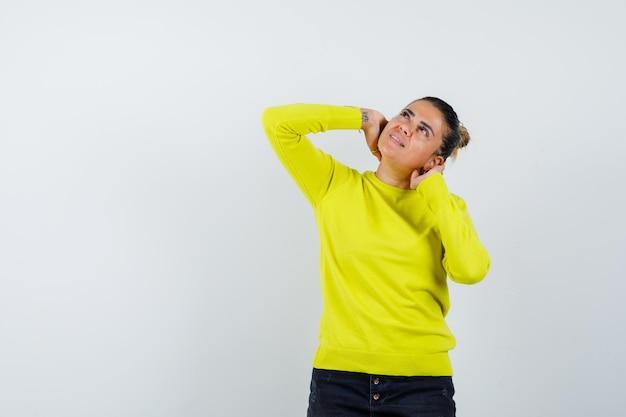 Mulher jovem com suéter amarelo e calça preta colocando as mãos atrás do pescoço, olhando para cima e parecendo pensativa