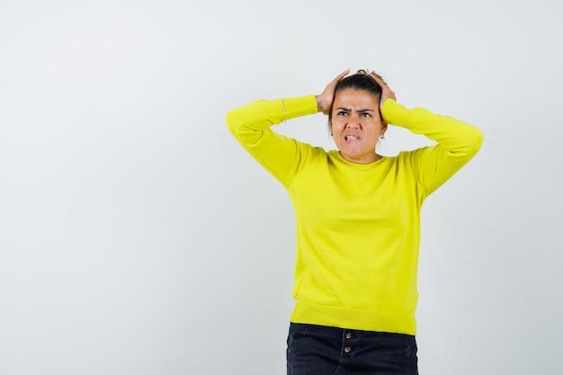 Mulher jovem com suéter amarelo e calça preta de mãos dadas na cabeça, mordendo os lábios e parecendo preocupada