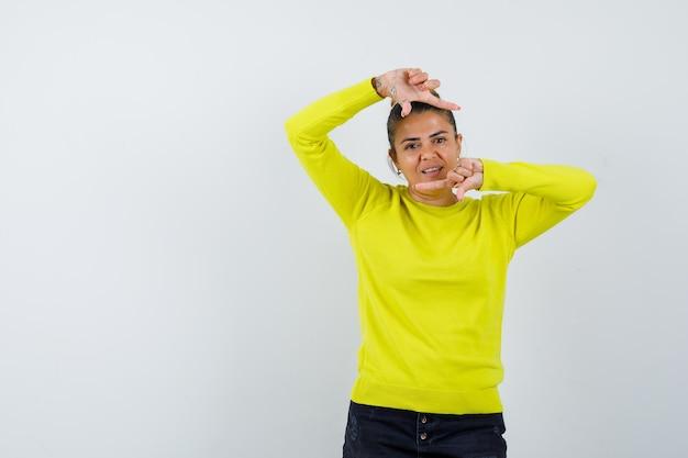 Mulher jovem com suéter amarelo e calça preta mostrando gesto de moldura e parecendo feliz