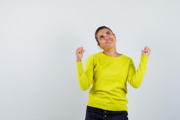 Mulher jovem com suéter amarelo e calça preta, mostrando o gesto de vencedor e parecendo feliz