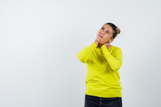 Mulher jovem com suéter amarelo e calça preta, sentindo dores no pescoço e parecendo preocupada