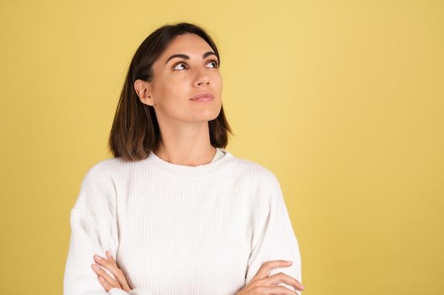 Mulher jovem com suéter branco quente pensativa com um sorriso