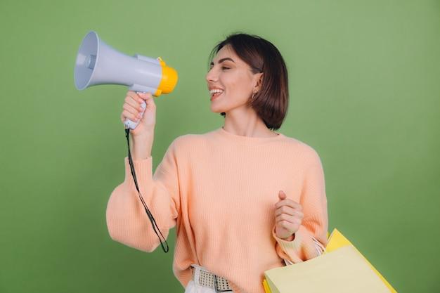 Mulher jovem com suéter casual cor de pêssego isolado na parede verde oliva grito no megafone segurando sacolas de compras e anuncia promoção de venda de descontos