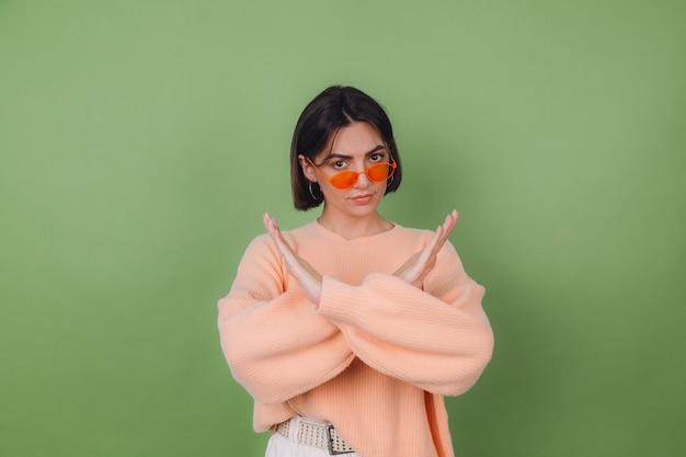 Mulher jovem com suéter casual de óculos laranja e pêssego, isolado na parede verde oliva, sério, mostrando gesto de pare com as mãos cruzadas, cópia espaço