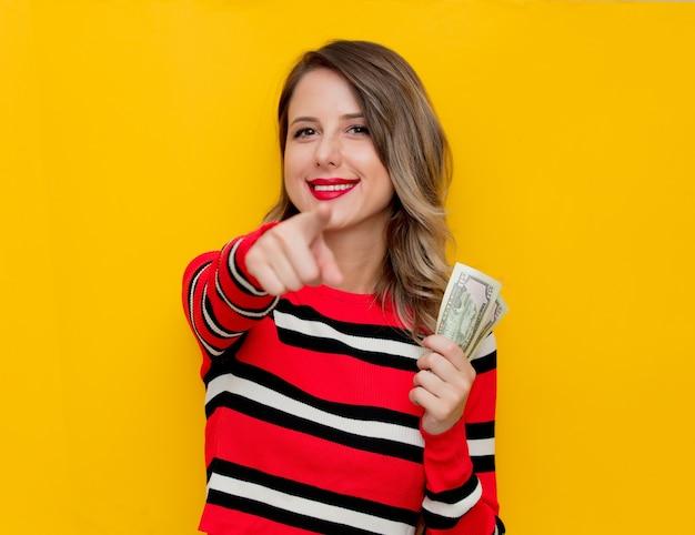 Mulher jovem com suéter listrado vermelho e dinheiro em amarelo