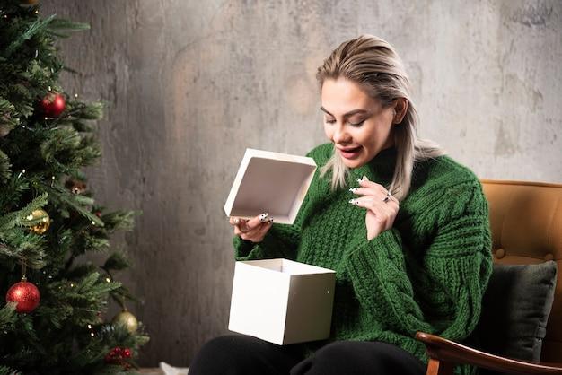 Mulher jovem com suéter verde quente animada com um presente