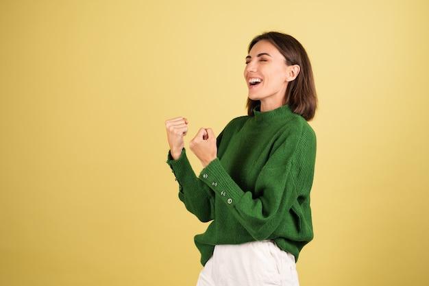 Mulher jovem com suéter verde quente animada, mostrando gesto de vencedor