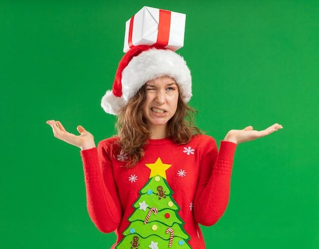 Mulher jovem com suéter vermelho de natal e chapéu de papai noel com um presente na cabeça, parecendo confusa e descontente, estendendo os braços para os lados em pé sobre um fundo verde