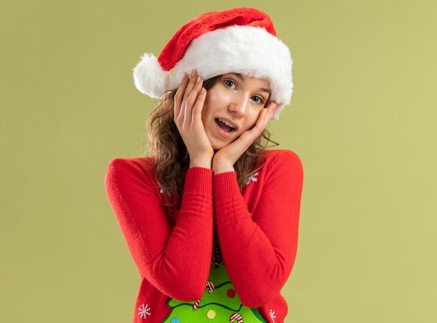 Mulher jovem com suéter vermelho de natal e chapéu de papai noel, parecendo feliz e sorridente.
