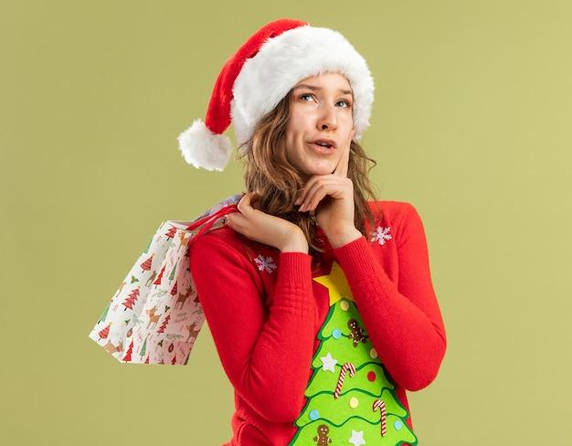 Mulher jovem com suéter vermelho de natal e chapéu de papai noel segurando sacolas de papel com presentes de natal, parecendo perplexa em pé sobre a parede verde