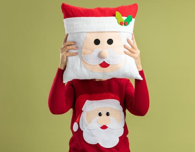 Mulher jovem com suéter vermelho de natal escondendo o rosto com uma almofada de natal em pé sobre a parede verde
