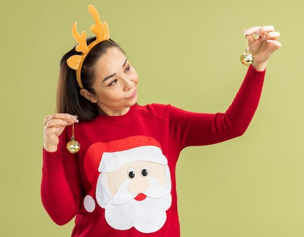 Mulher jovem com suéter vermelho de natal, vestindo uma borda engraçada com chifres de veado segurando bolas de natal, parecendo confusa e com dúvidas